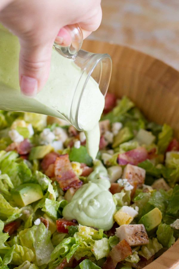 Pouring Avocado Ranch Salad Dressing on salad