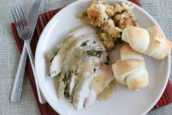 turkey breast on a plate with rolls and stuffing