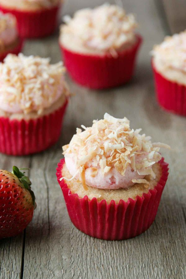 Strawberry, coconut and pineapple cupcakes topped with coconut frosting and toasted coconut