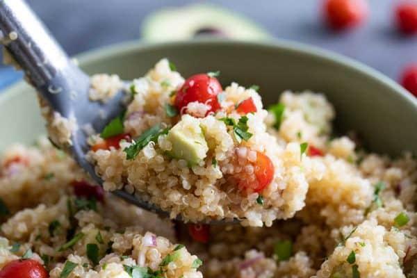 scoop of quinoa salad with avocado and tomato