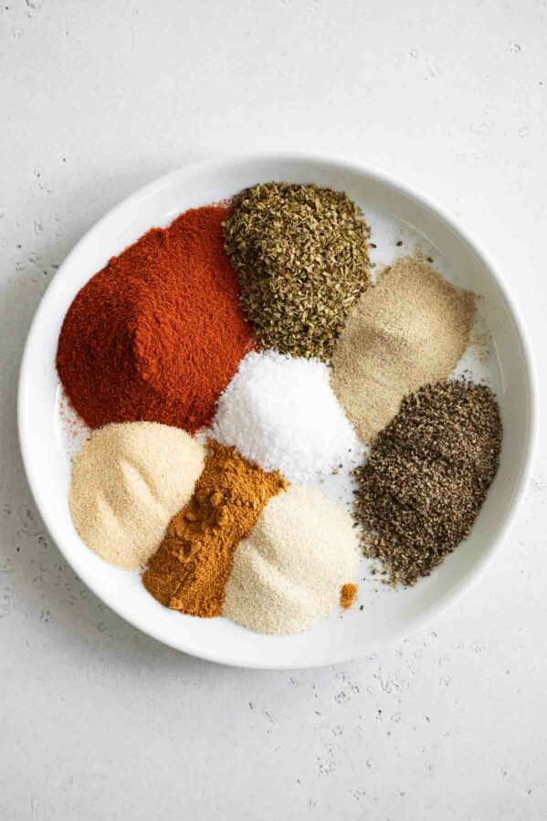 piles of spices needed to make homemade cajun seasoning