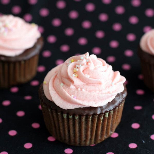 chocolate cupcakes topped with pink buttercream and sprinkles