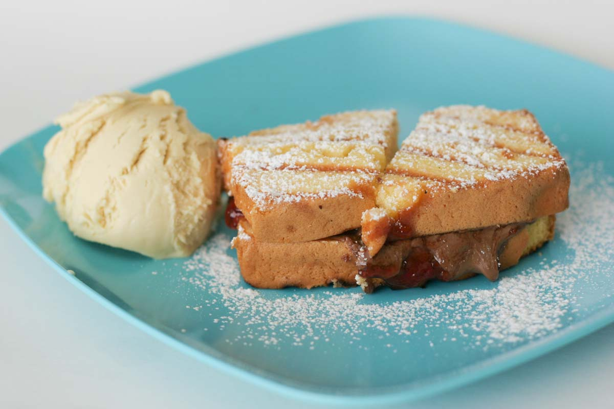 Grilled dessert sandwich with pound cake, jam and chocolate with a scoop of ice cream