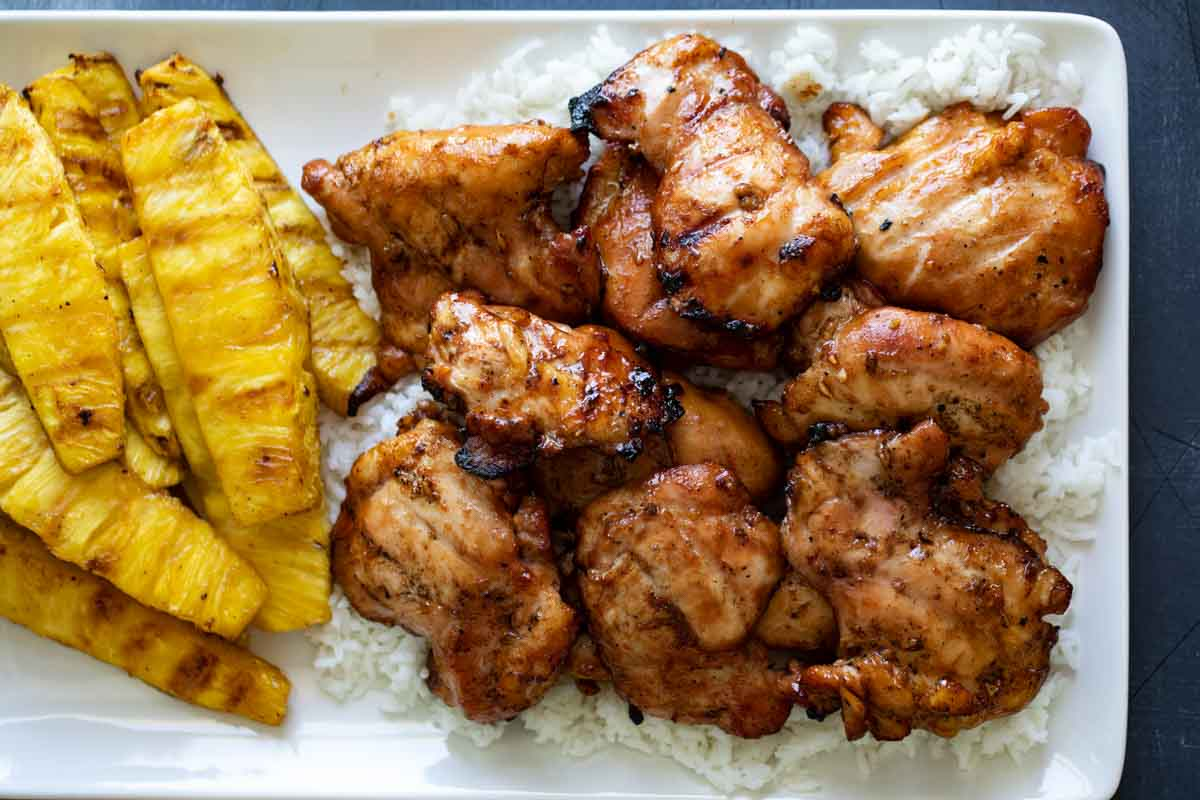 grilled chicken on a plate with rice and grilled pineapple