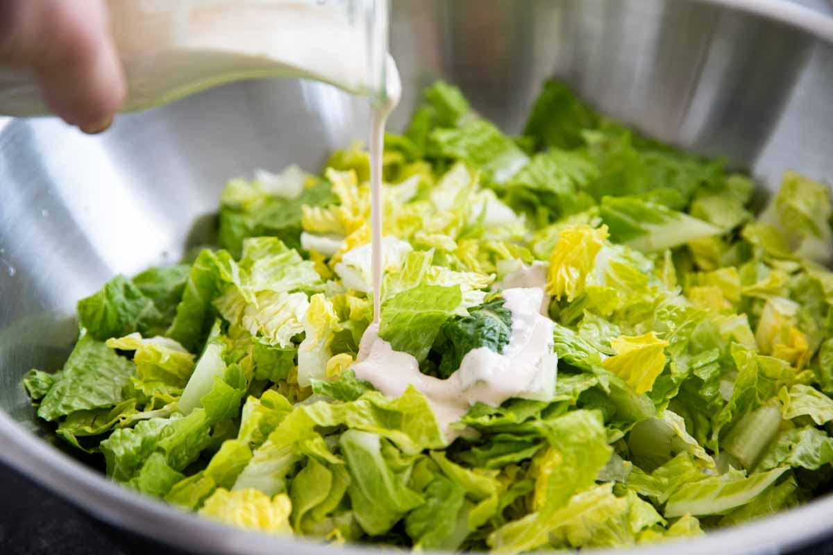 pouring Caesar dressing over greens