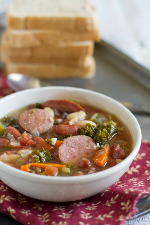 bowl of soup with sausage, beans and vegetables