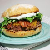Burger with bacon, cheese, sour cream and arugula