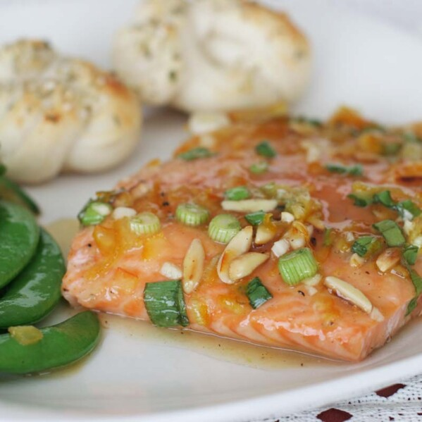 plate with citrus glazed salmon, sugar snap peas and parmesan rolls