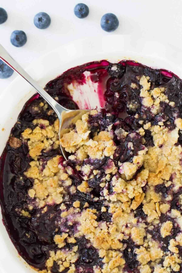 Dish of blueberry crisp with serving spoon