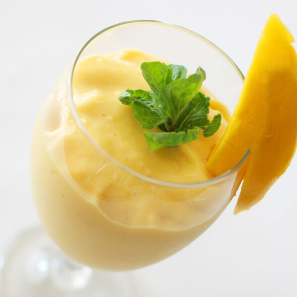 Mango Batido in a glass with mint and fresh mango