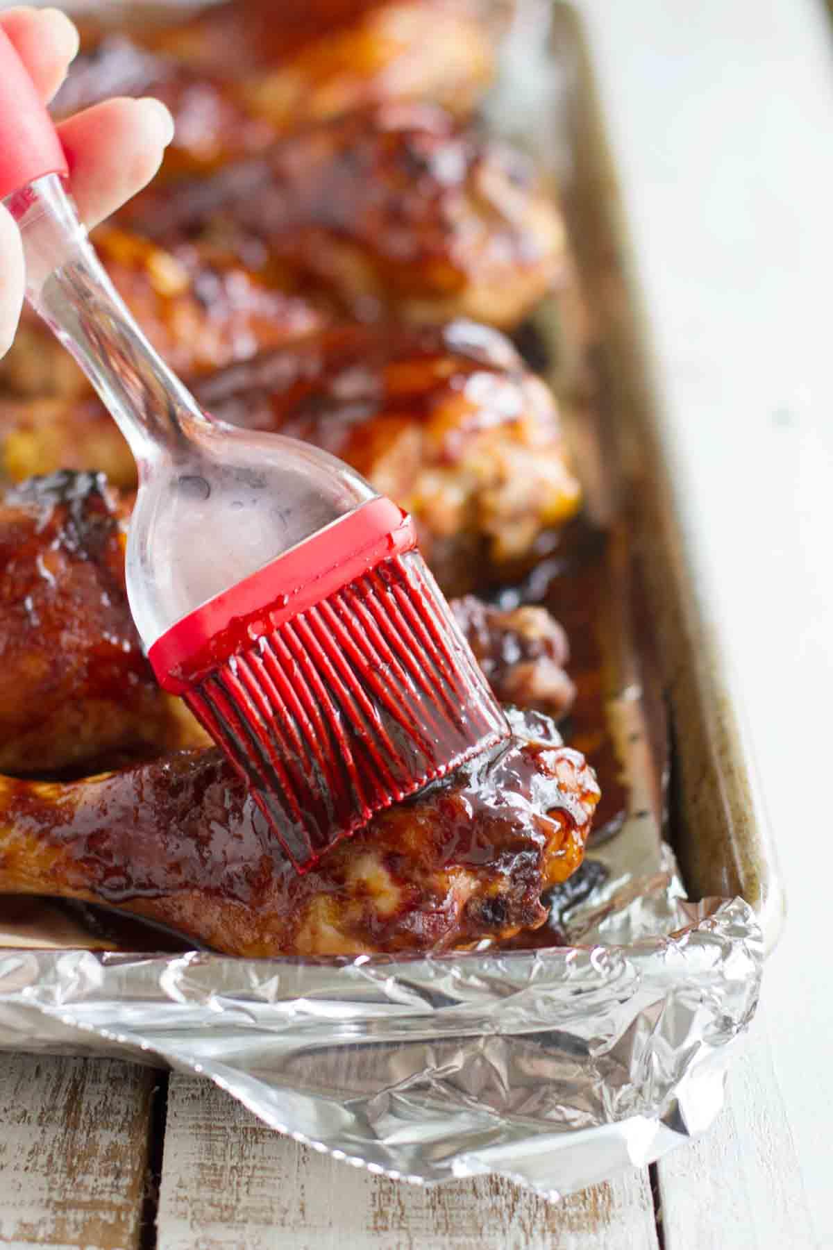 brushing sauce on chicken drumsticks
