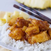 pineapple chicken over rice on a plate