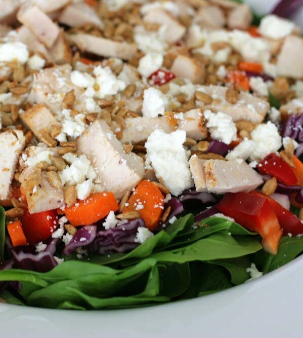 salad topped with chicken, vegetables and crumbled cheese