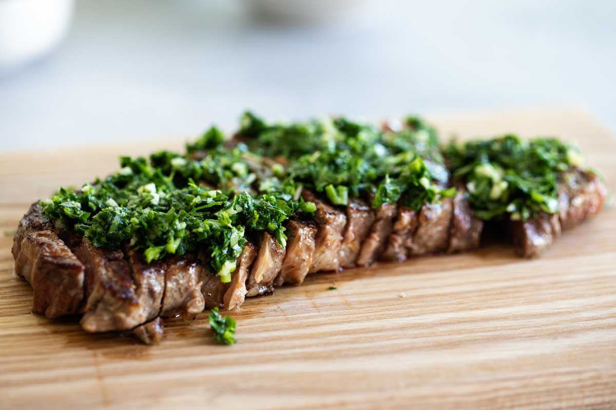grilled steak topped with chopped parsley