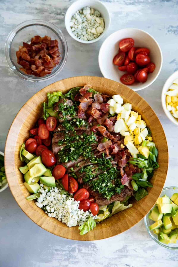 top view of steak cobb salad with bowls of ingredients on the side