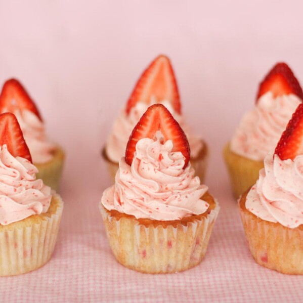 6 strawberry cupcakes with strawberry slices on top.