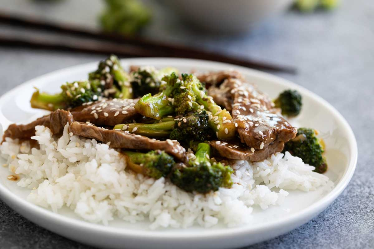 beef and broccoli over rice on a plate