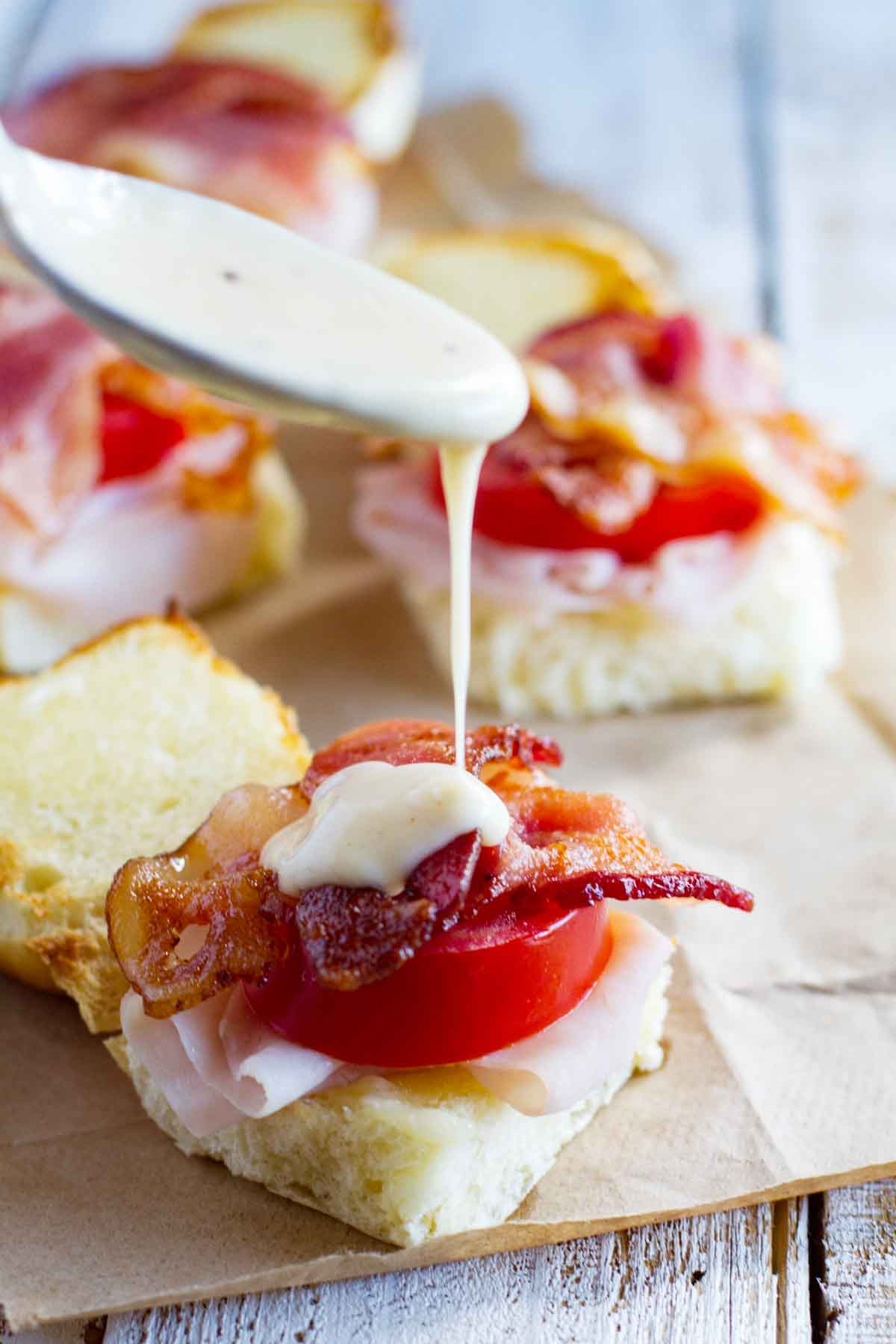 putting Mornay sauce over easy hot brown sandwiches