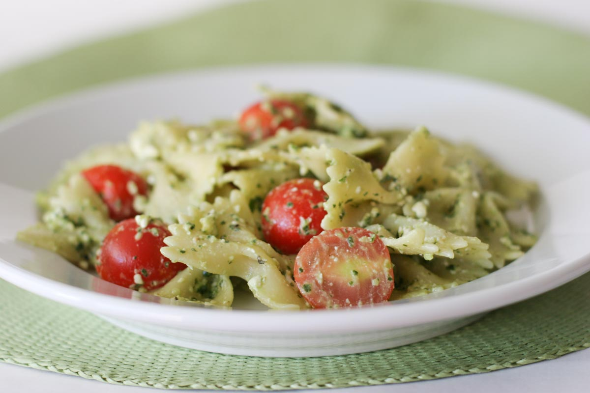 Pasta with Pesto, Feta and Cherry Tomatoes in a white bowl