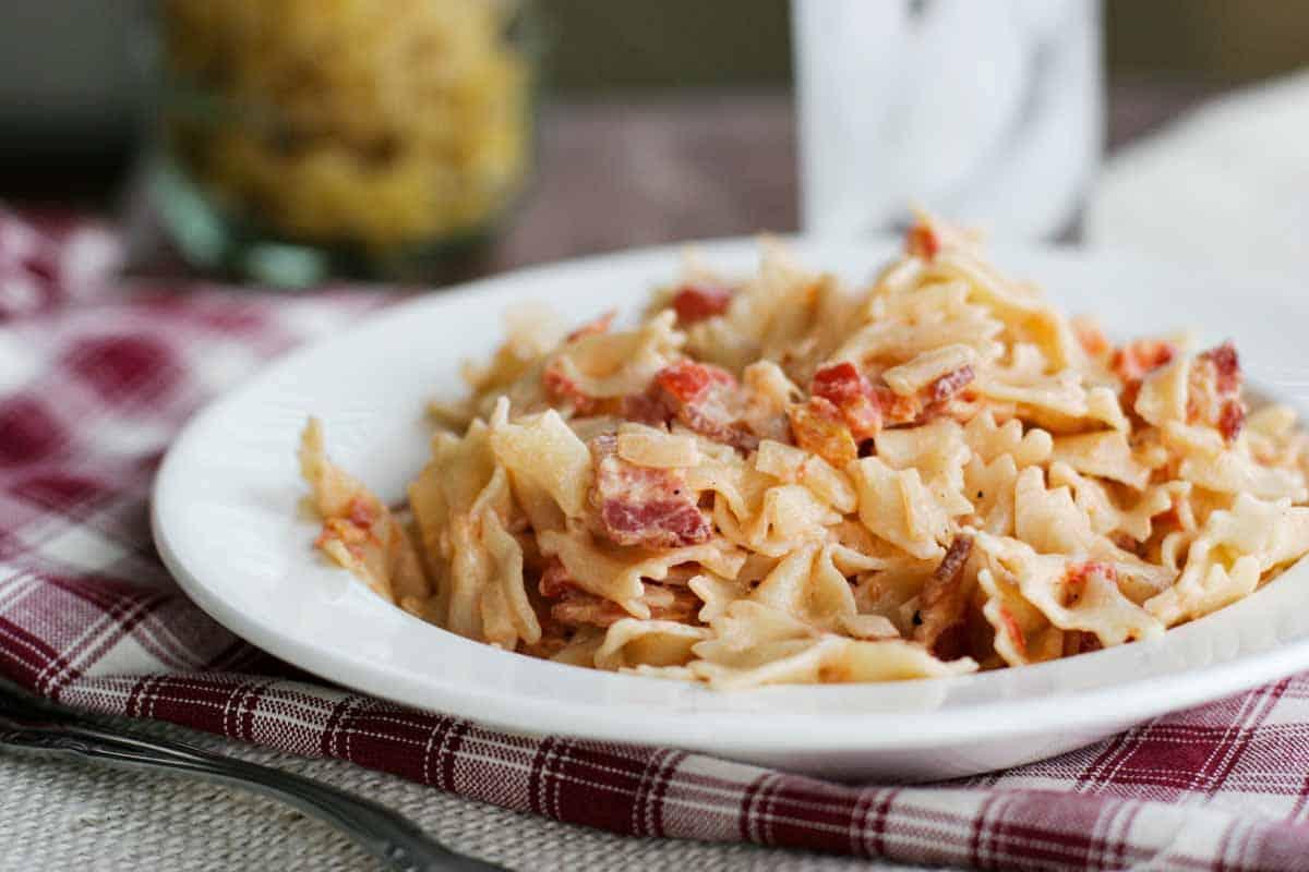 white plate with tomato bacon pasta