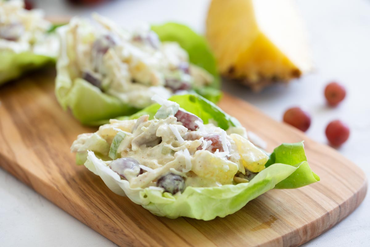 chicken lettuce wraps with pineapple, grapes and coconut on a cutting board