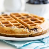 thick blueberry waffle on a white plate with syrup dripping