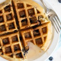overhead view of blueberry waffle with syrup with a bite taken