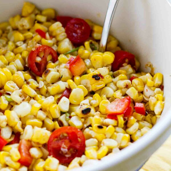 bowl filled with grilled corn salad with cherry tomatoes and peppers