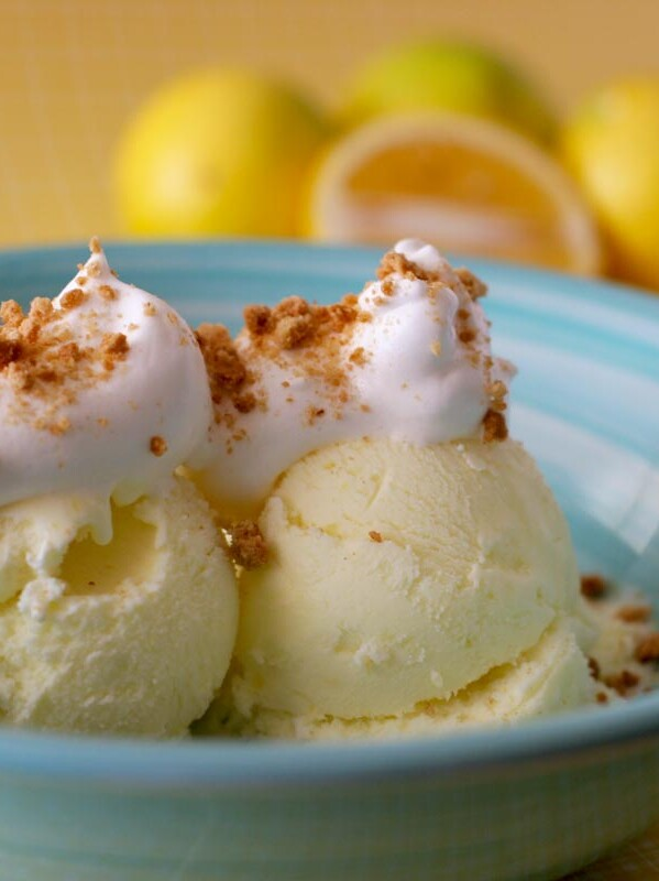 lemon ice cream in a bowl topped with homemade marshmallow sauce and graham cracker crumbs