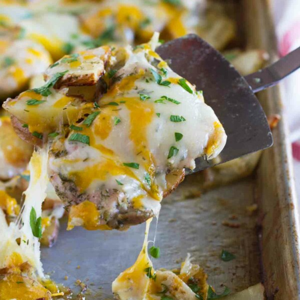 scooping chicken covered in cheese from a sheet pan