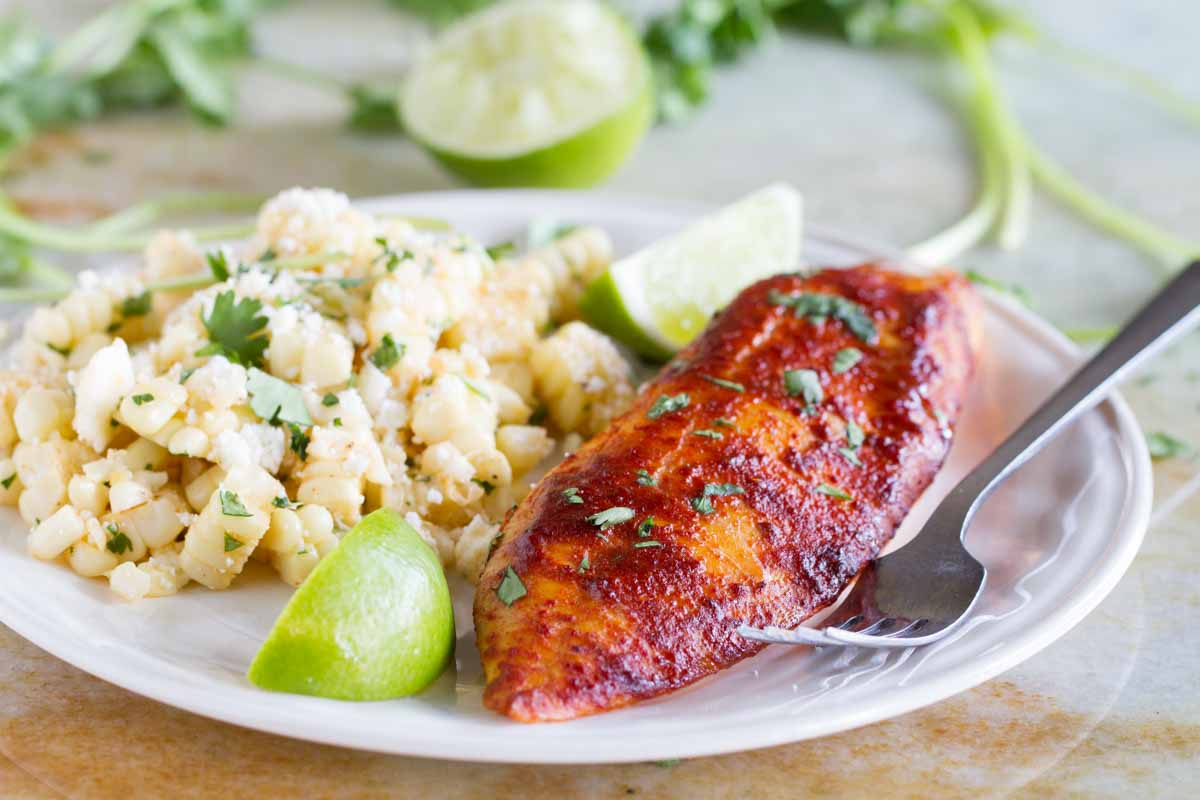White plate with taco seasoned grilled fish, corn salad and lime wedges