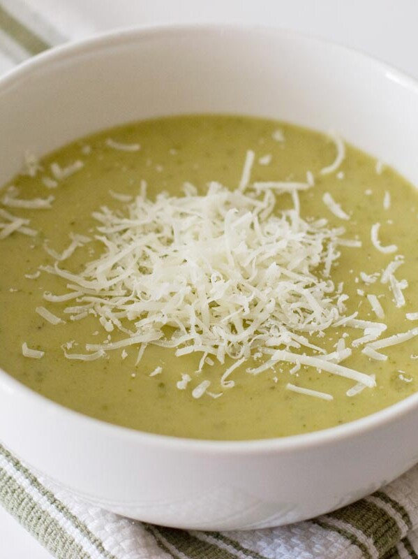 white bowl with zucchini soup with shredded parmesan cheese on top