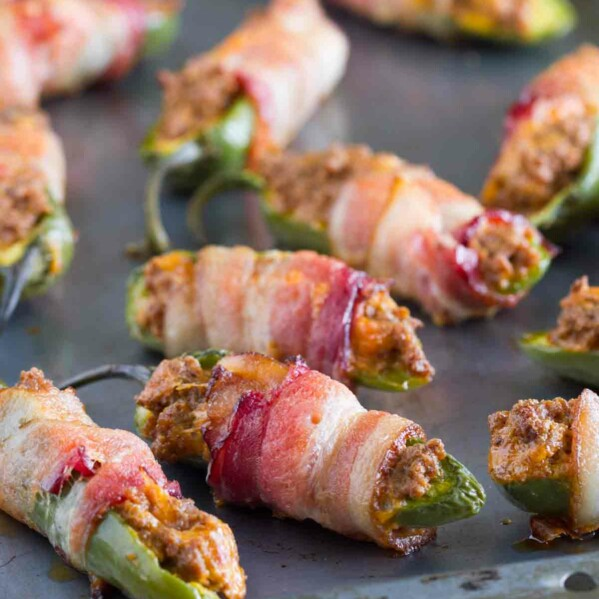 bacon wrapped jalapeno poppers with taco filling on a baking sheet