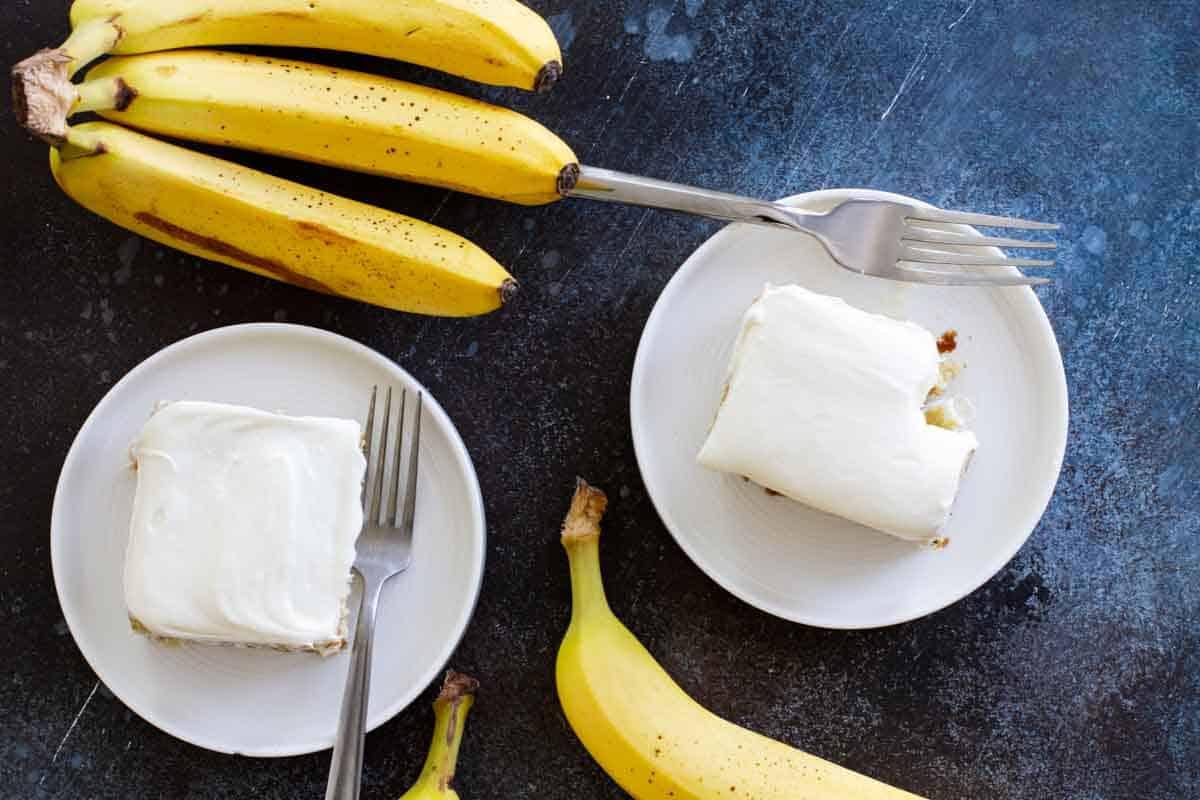 overhead view of banana cake on plates with ripe bananas