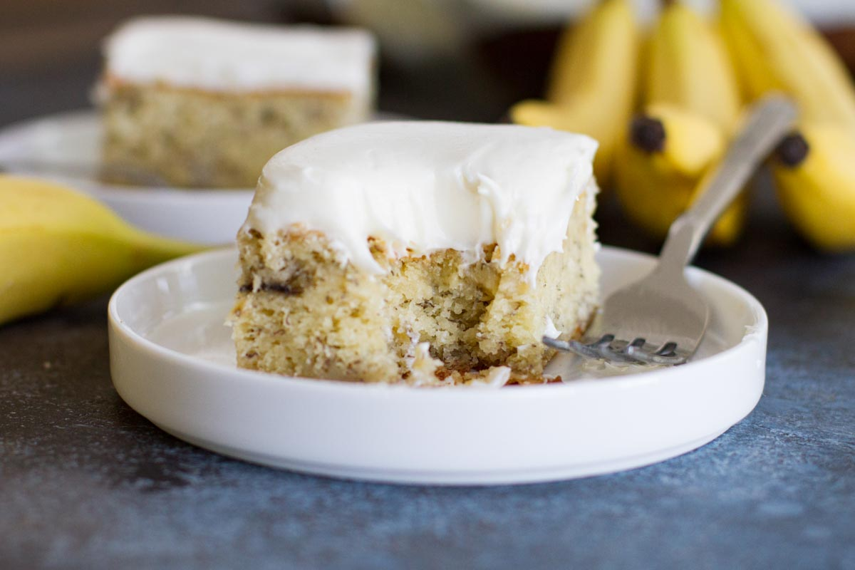 slice of banana cake with cream cheese frosting with bite taken