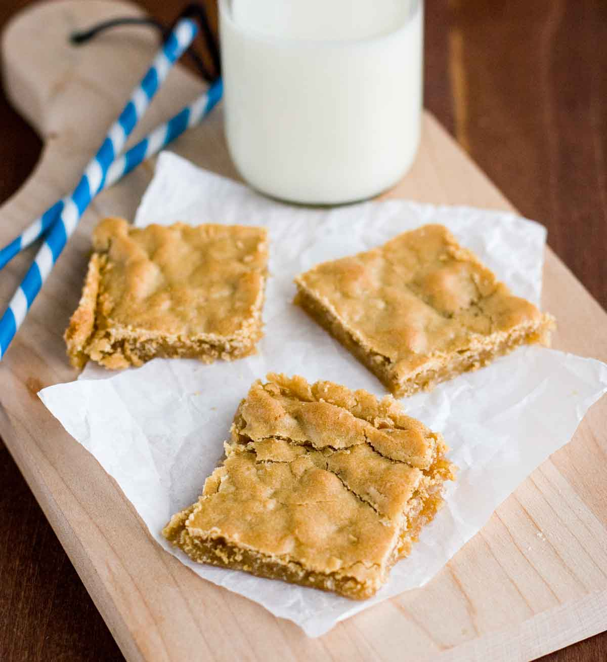 sliced Butterscotch Bars on a cutting board with milk and straws