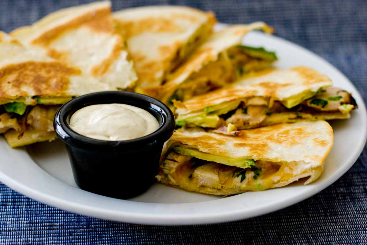 plate with sliced quesadillas with chicken, avocado and caramelized onions with dipping sauce