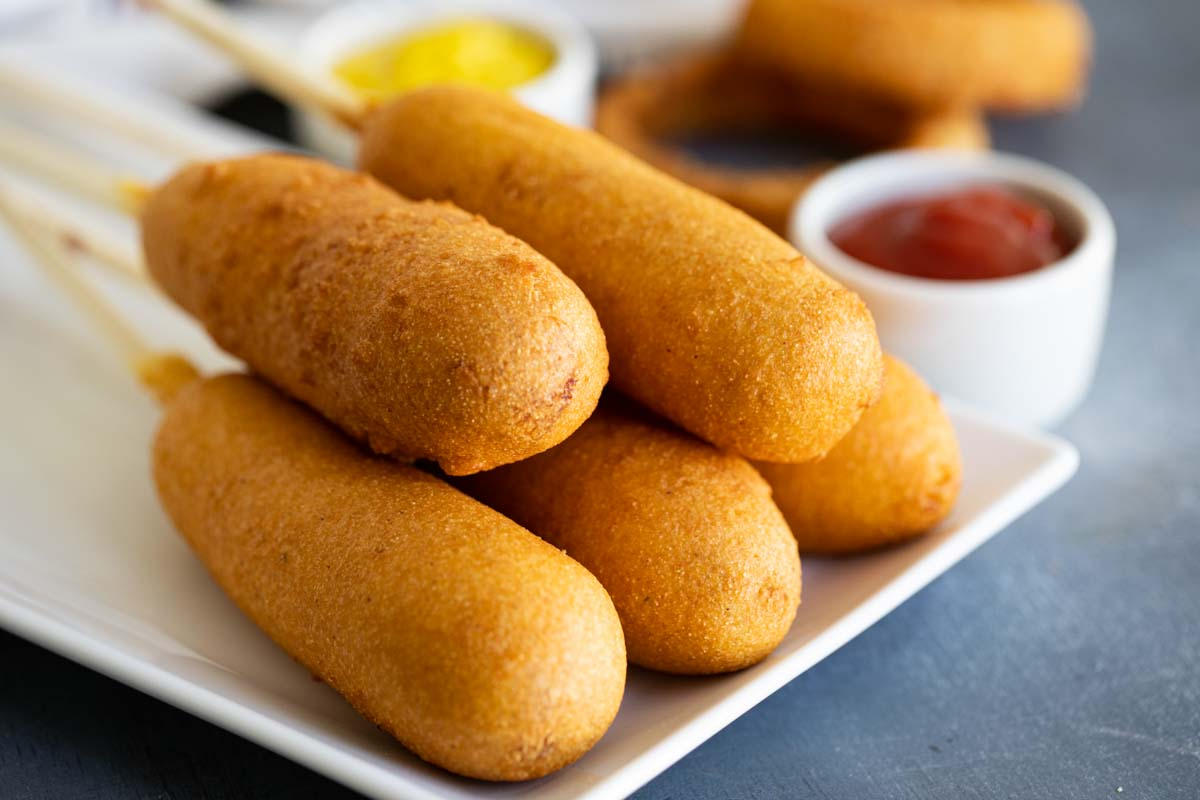 homemade corn dogs on a plate with ketchup and mustard