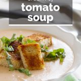 bowl of tomato soup topped with croutons and basil with text overlay