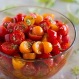 yellow and red grape tomatoes with herbs in a bowl