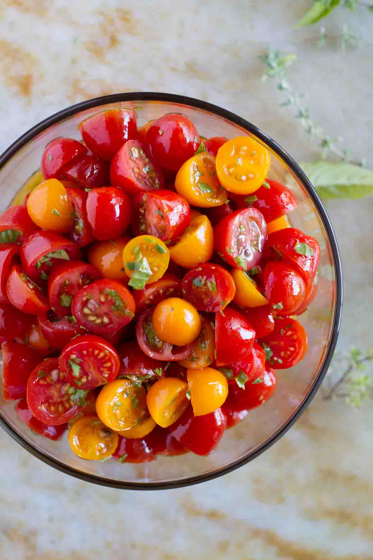 overhead view of sliced grape tomatoes with olive oil and herbs