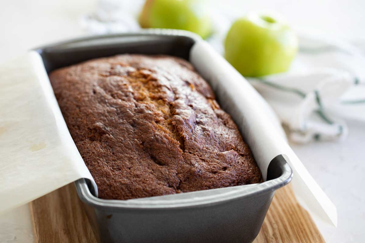 loaf of quick bread in a loaf pan with apples