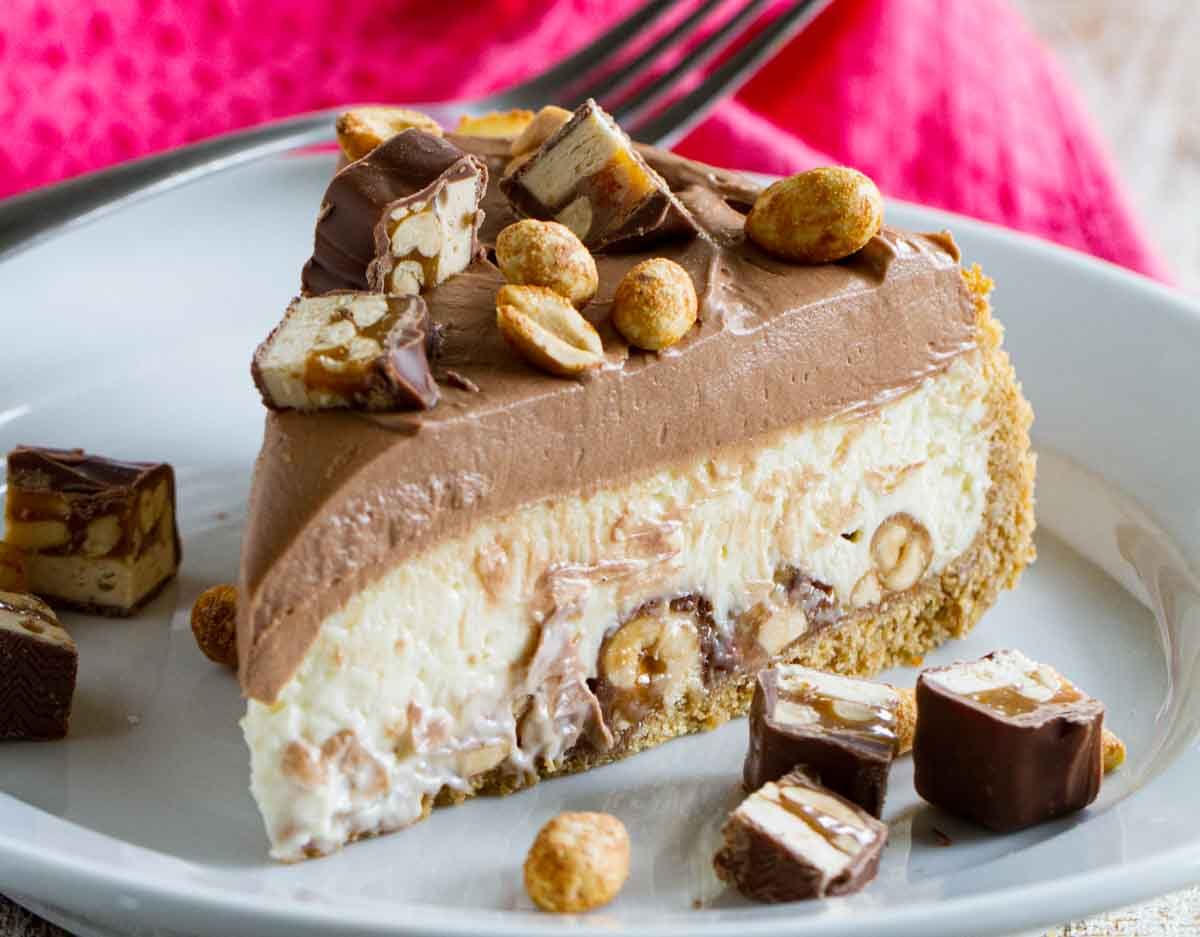 slice of snickers cheesecake with snickers chunks on the side