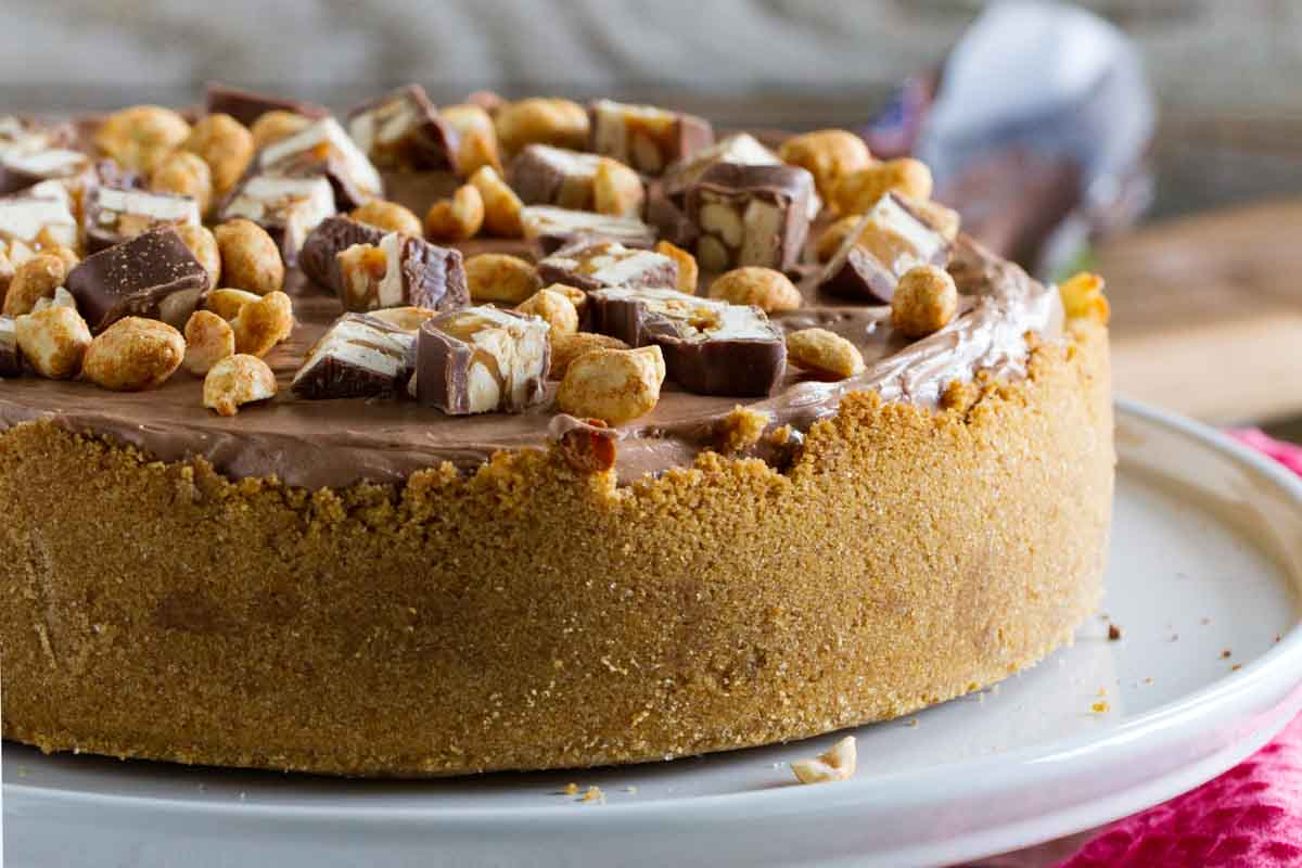 full snickers cheesecake on a serving platter