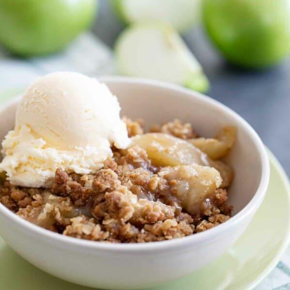 bowl of apple crisp topped with vanilla ice cream