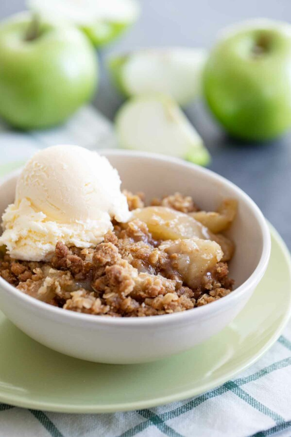 bowl of apple crisp topped with vanilla ice cream