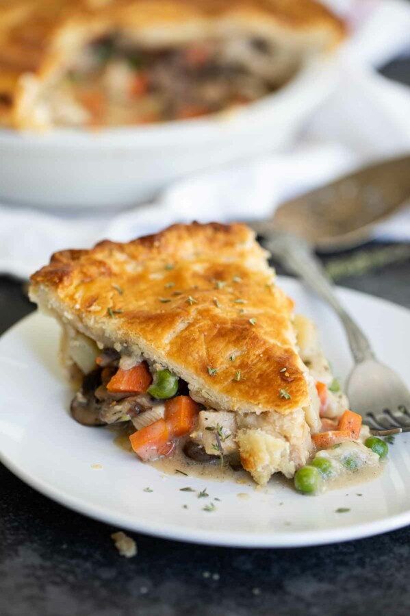 slice of chicken pot pie on a plate with the pan in the background