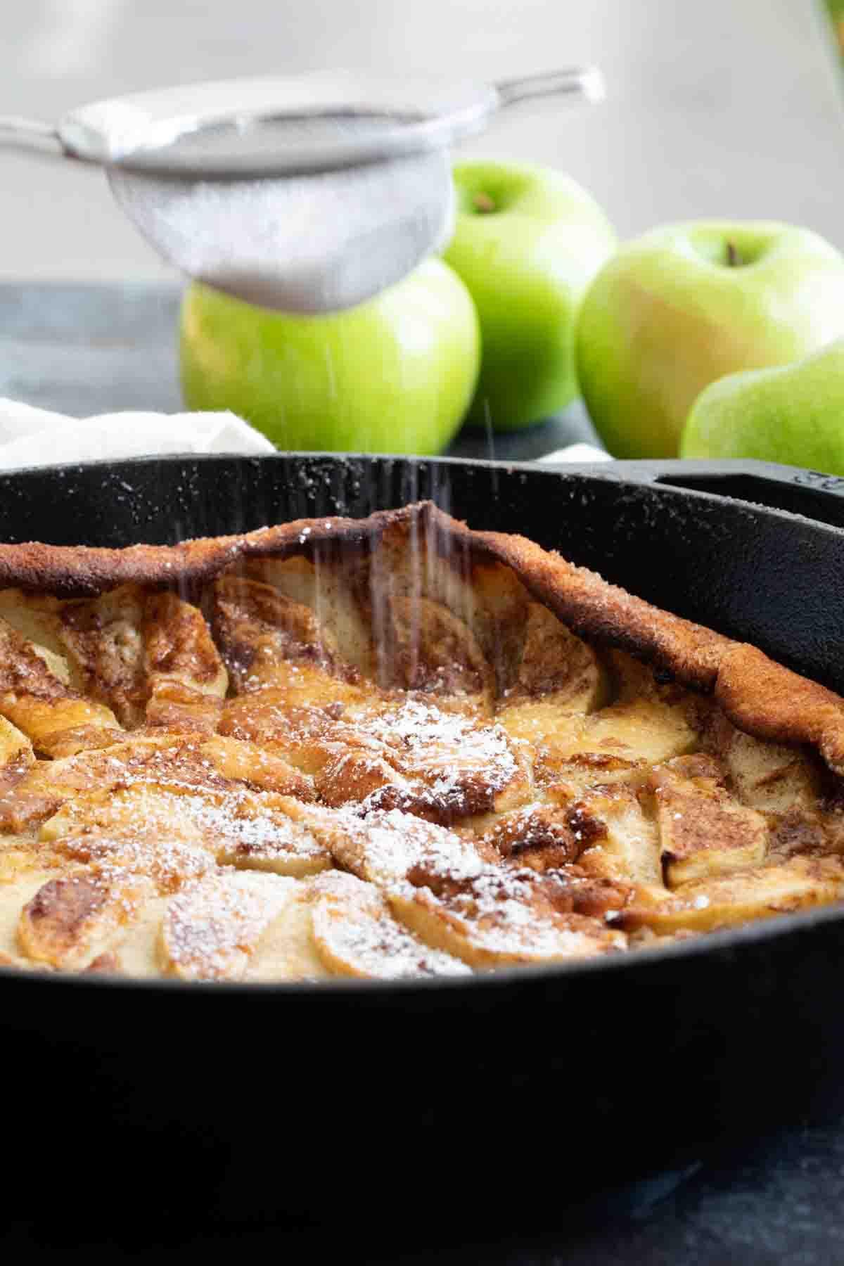 shaking powdered sugar onto a German Apple Pancake