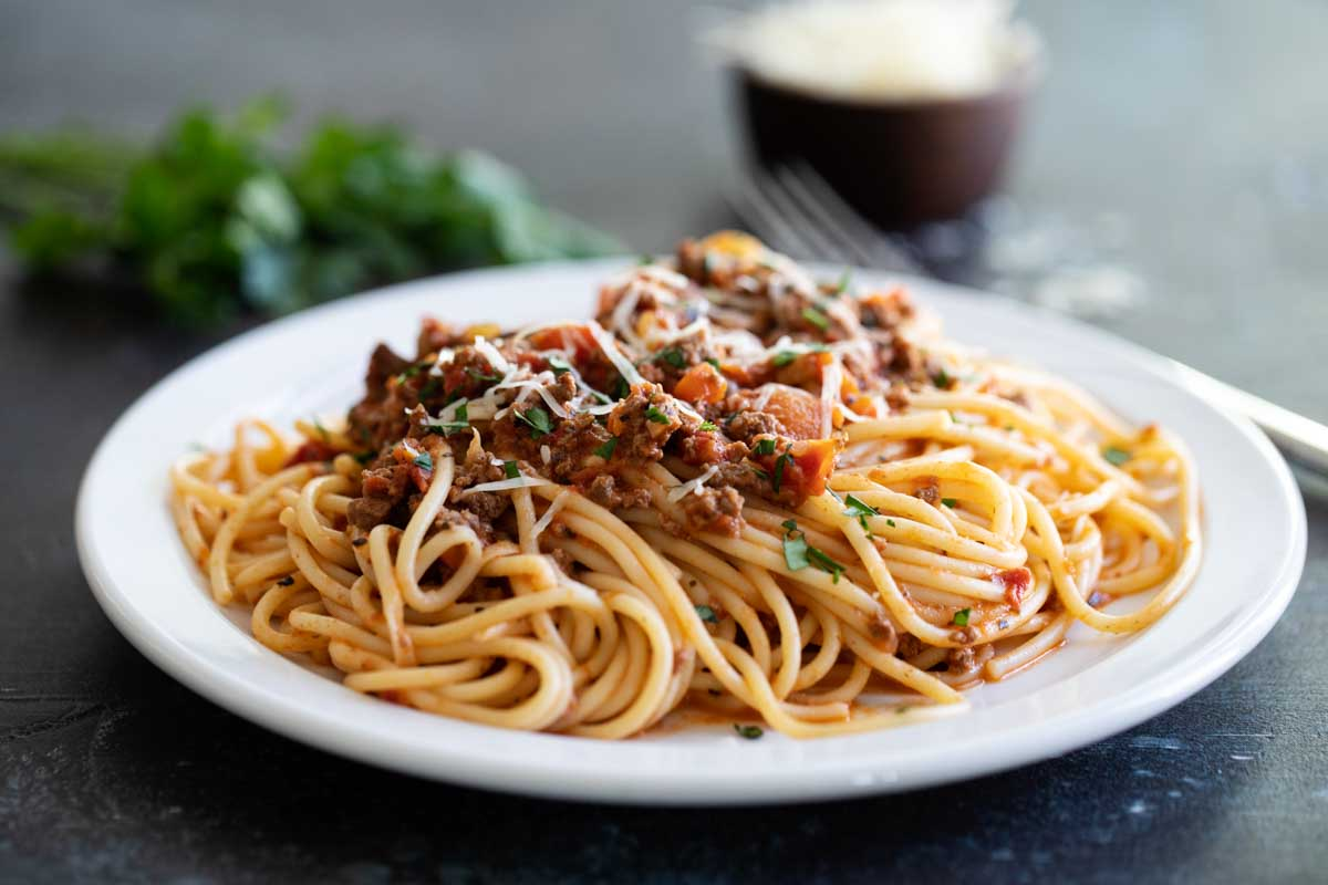 plate with pasta and bolognese topped with parsley and cheese