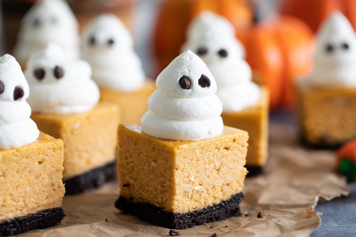 pumpkin cheesecake bars topped with whipped cream ghosts